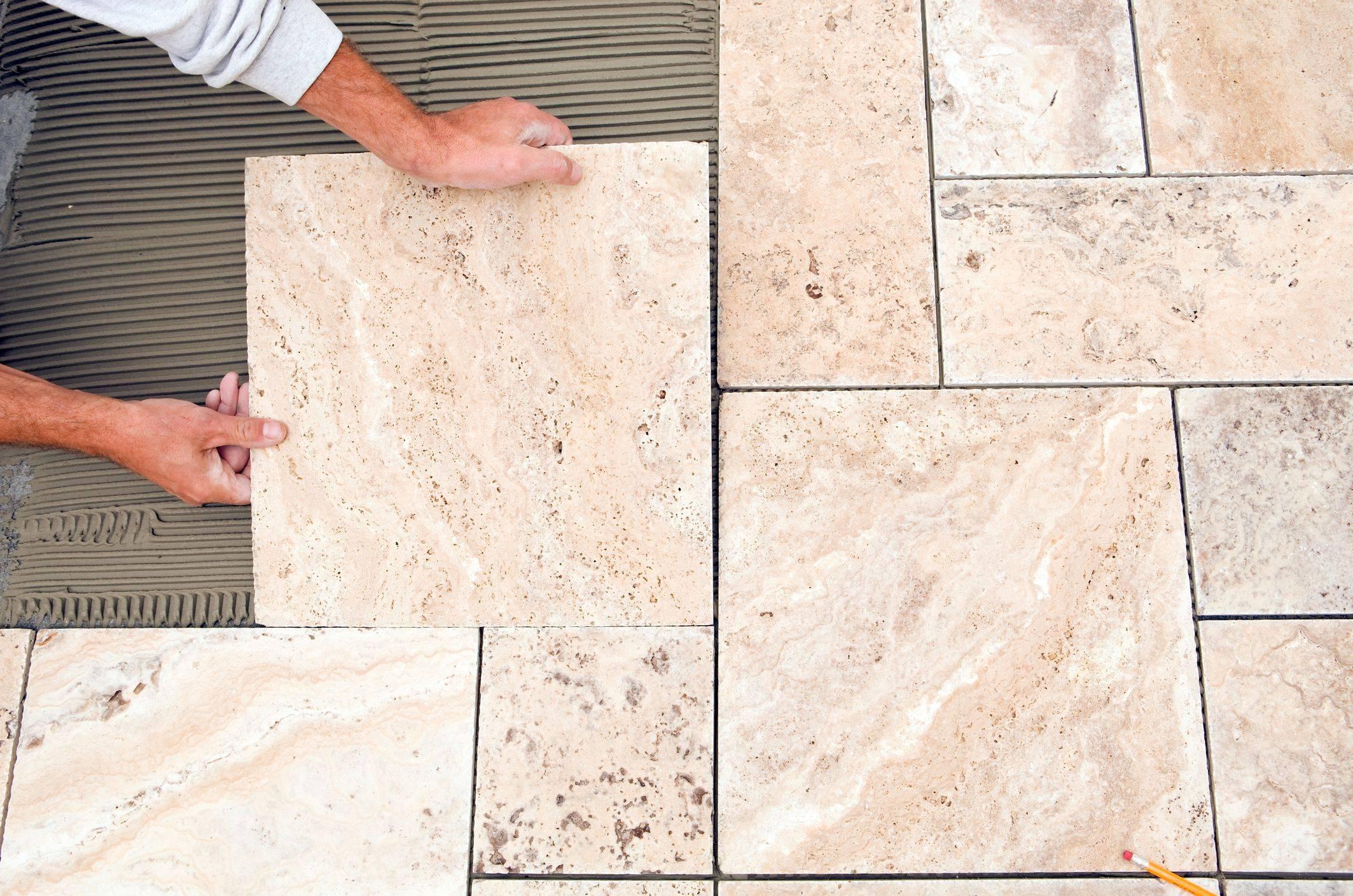 worker places new tile on a bathroom floor 37f501b04b5d401cb5ca7edcdd8686b5