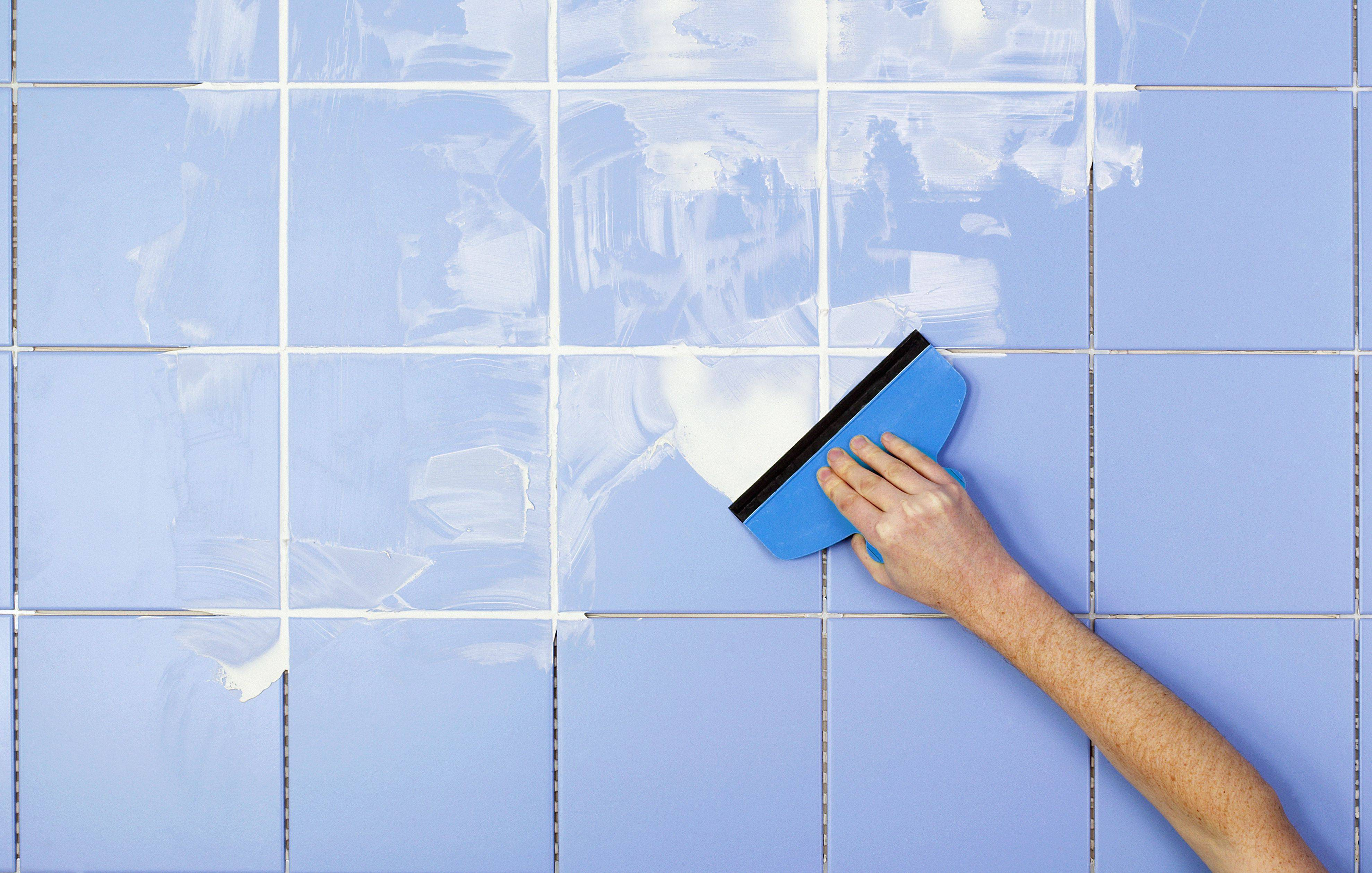 hand spreading grout on tiles with grout spreader 583c5e073df78c6f6a2f22b6