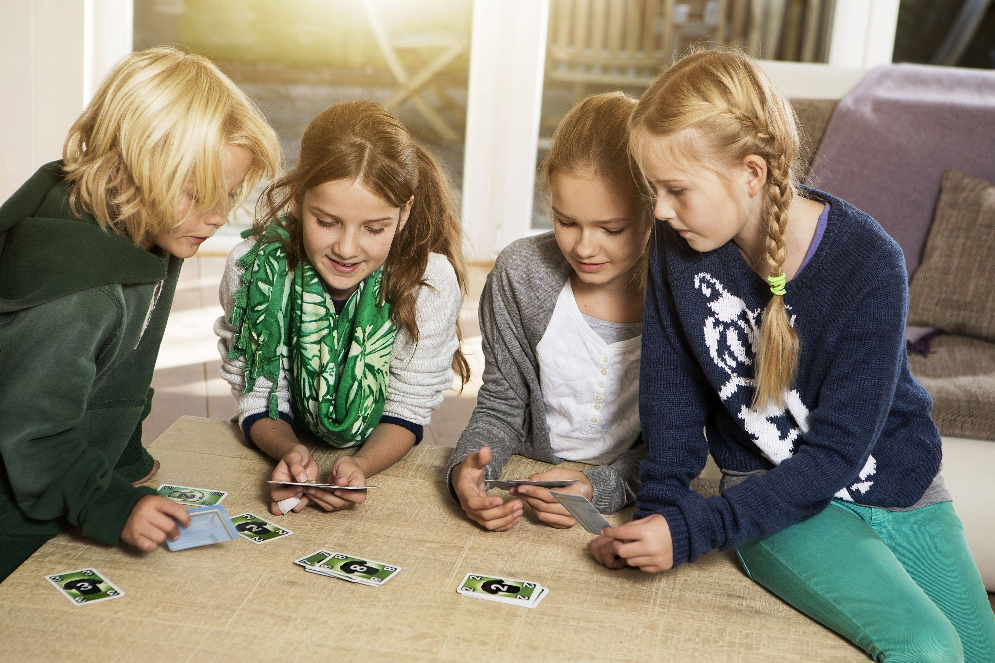 four children playing card game in living room 5ade2c6aa9d4f c673e