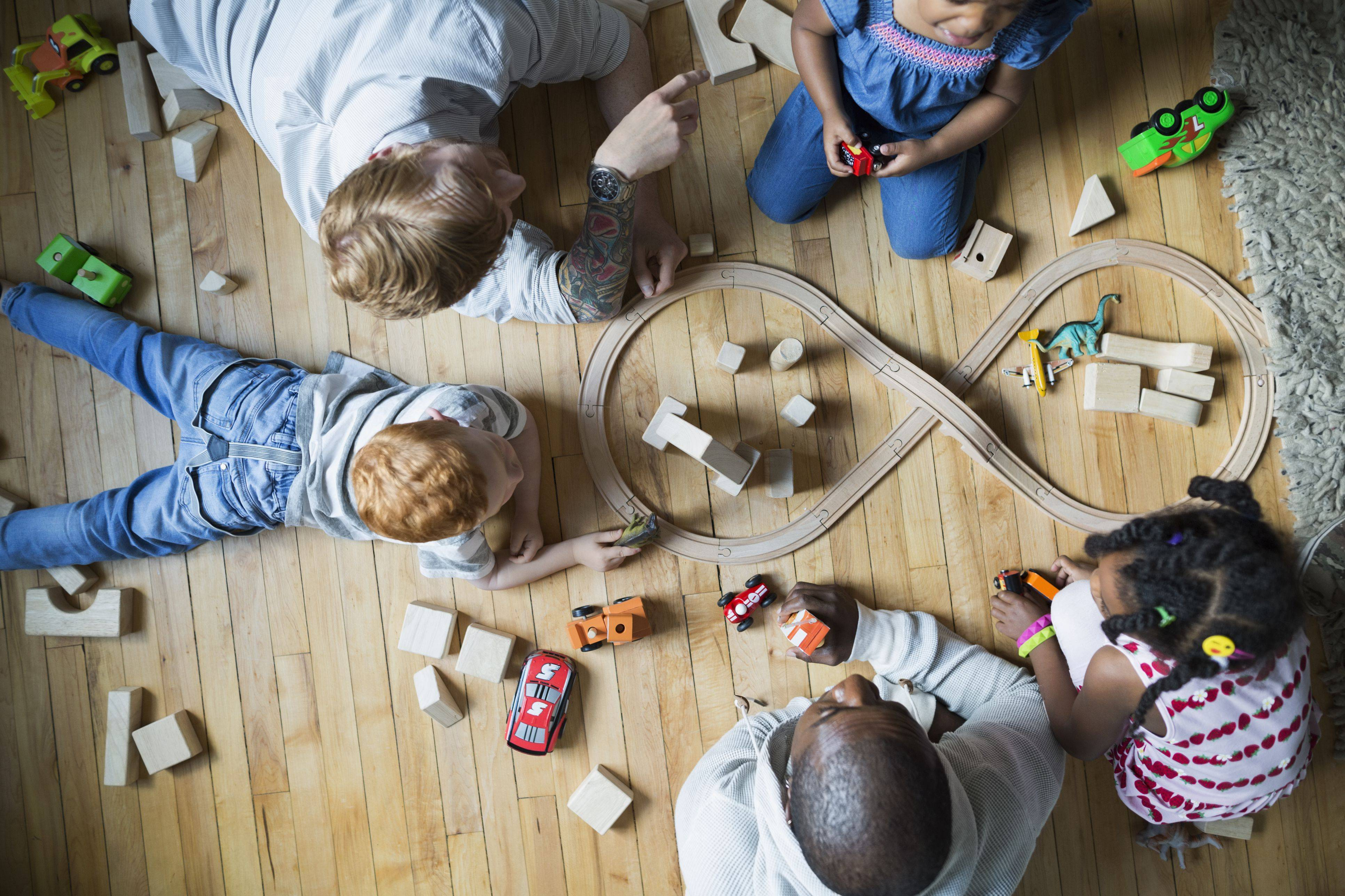 overhead view fathers and children enjoying play date playing with toy train and wood blocks 5a eda a90f8