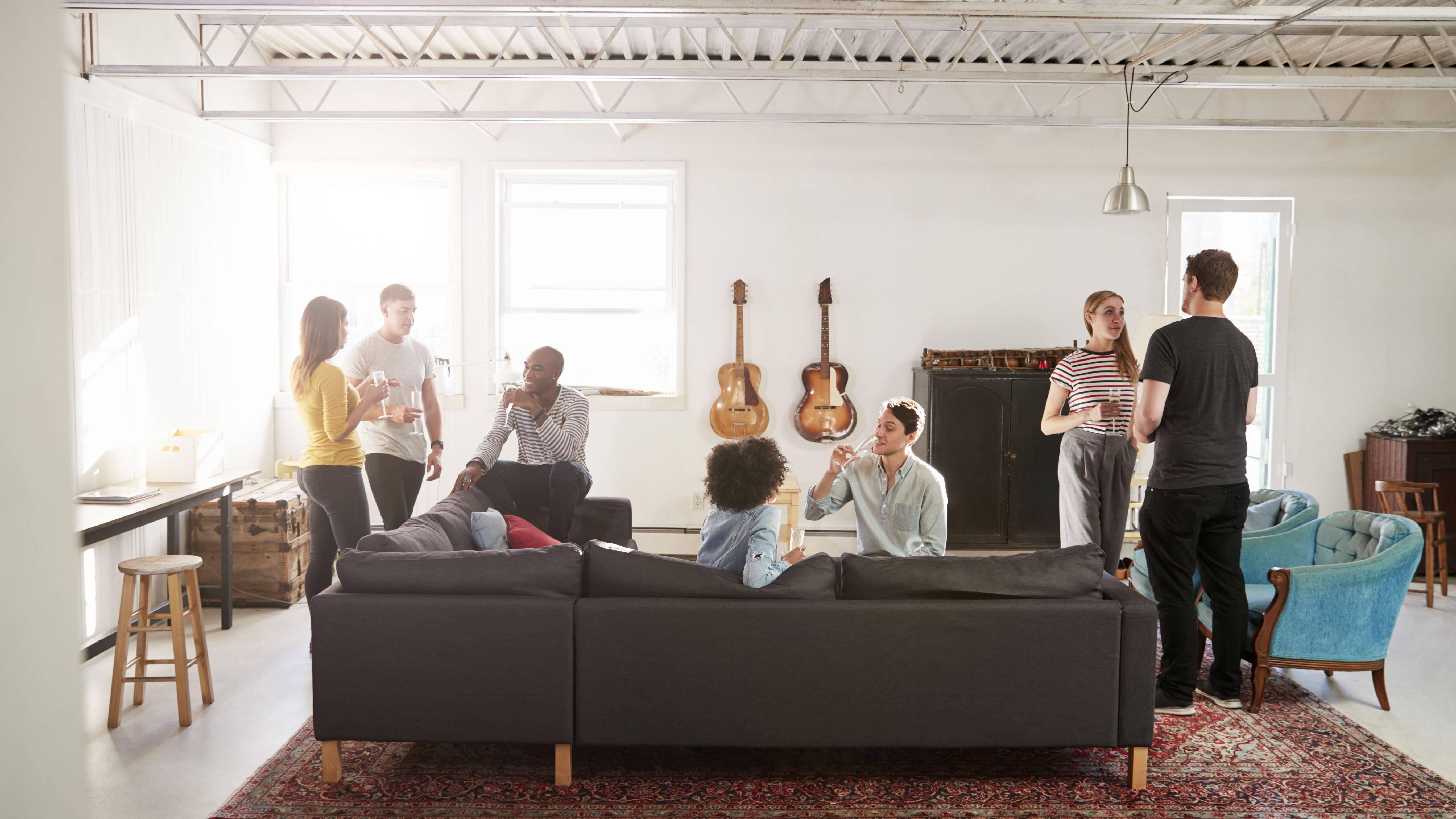 friends at a party in a new york loft apartment full length ccdf44a4c14e4873a5a2b5df46b82ca4