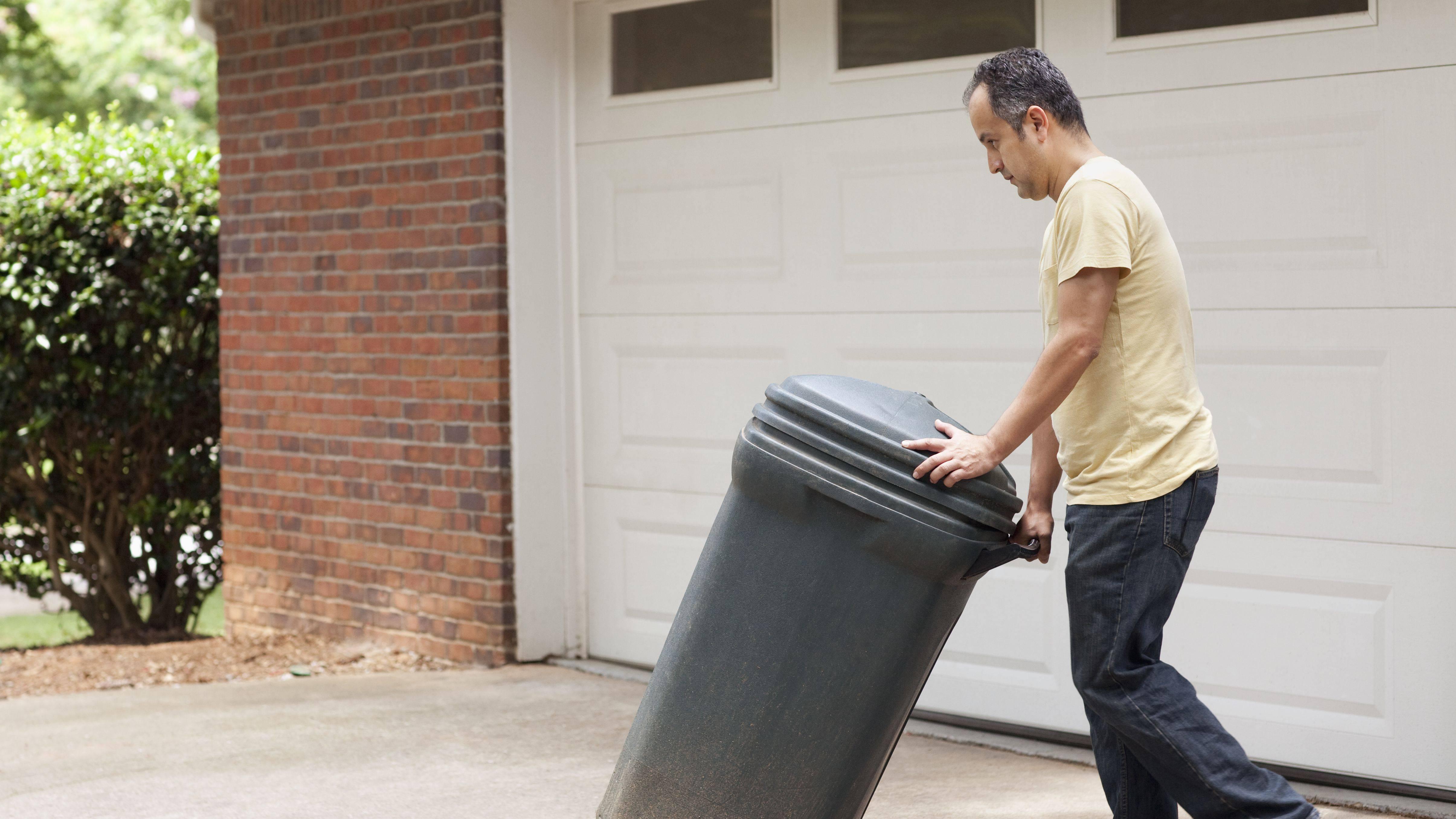 hispanic man rolling garbage can 5b043cc6fa6bcc d1e