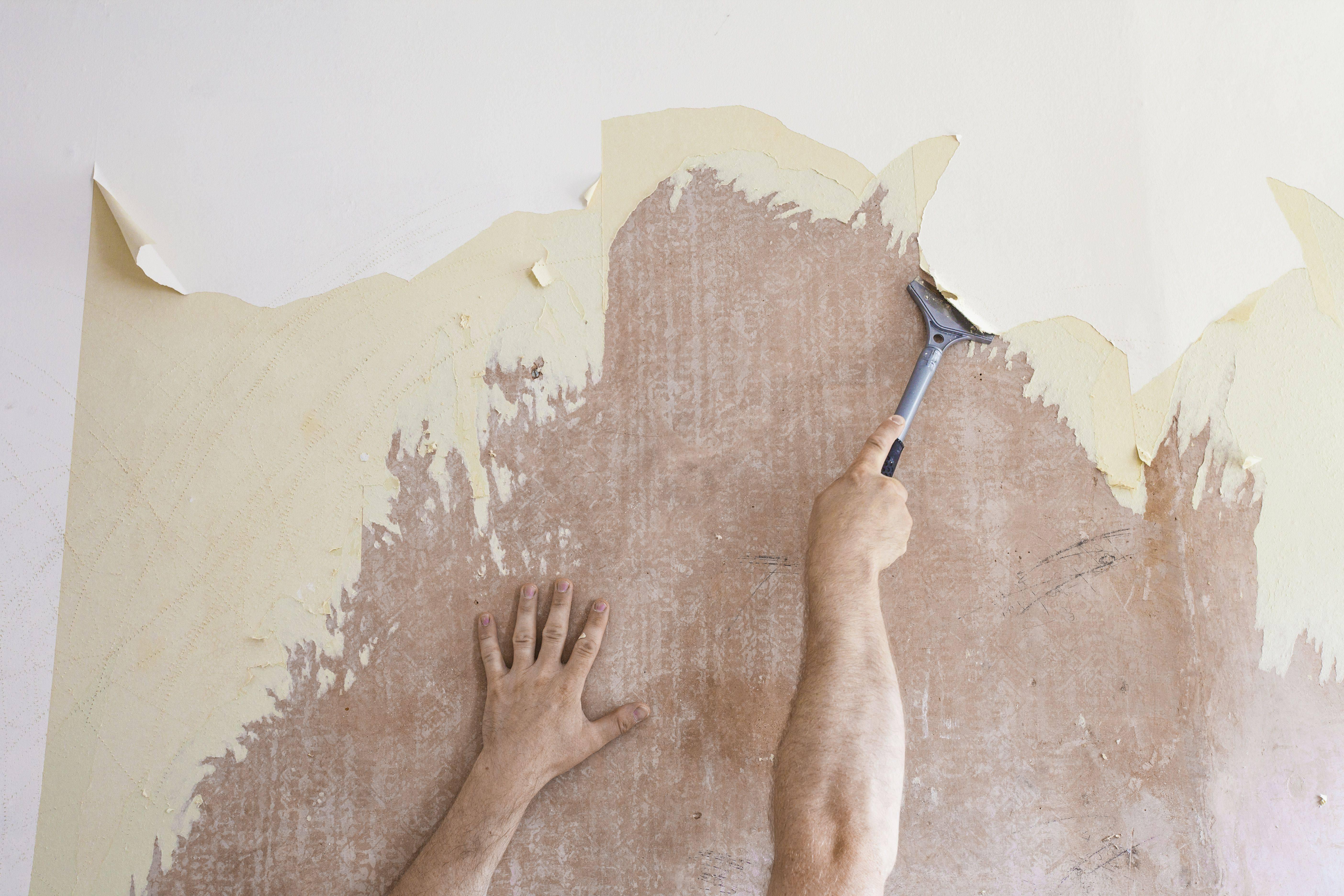 mature man using scraper to scrape off old wallpaper 5a d642dca001a3ddb74