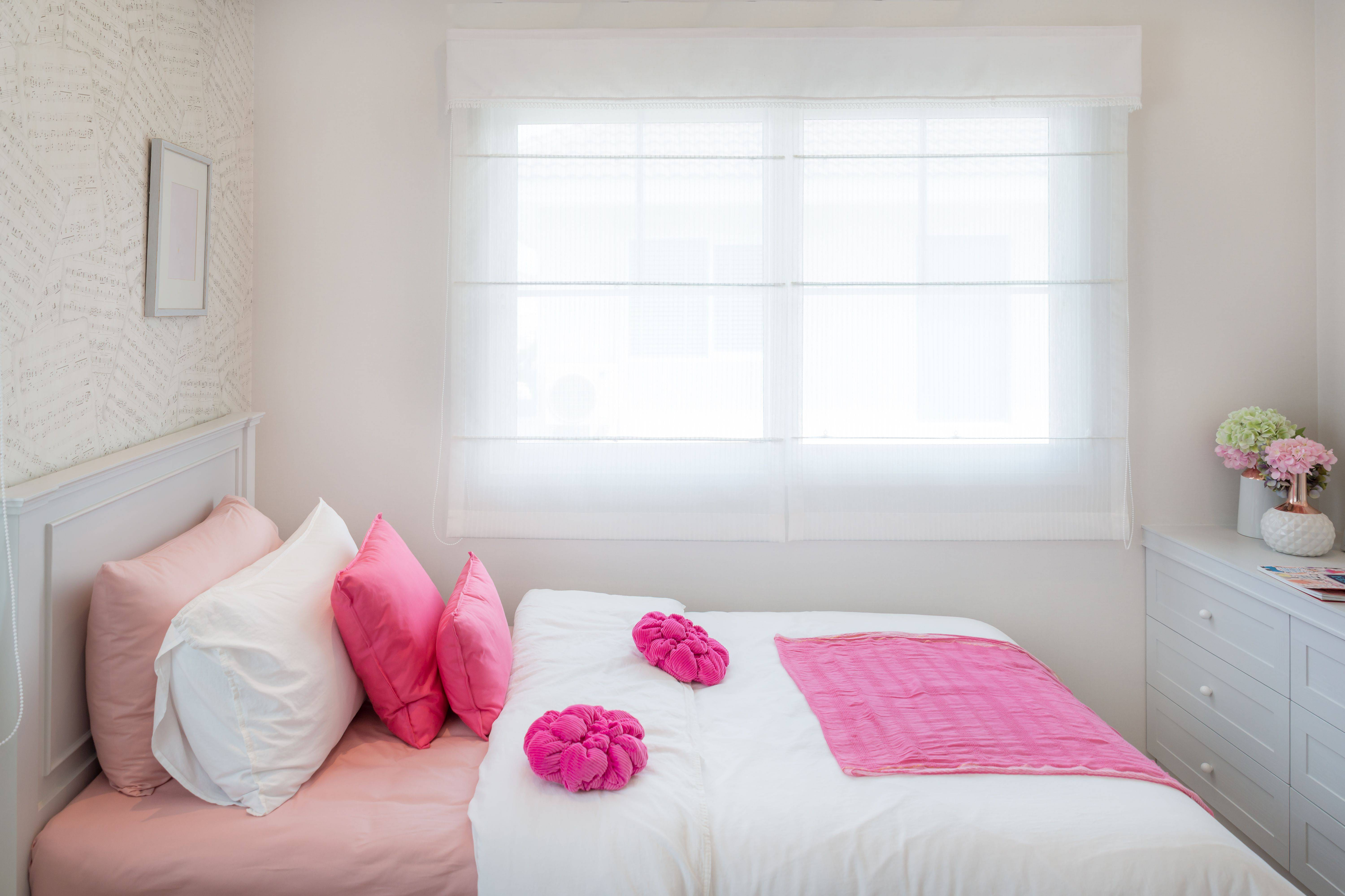 interior of white bedroom with double bed and pink pillows and bookshelf at home 5abcff506bf b7bc